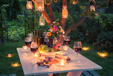 Beautiful table full of cheese and meats in garden at dusk - 122699418