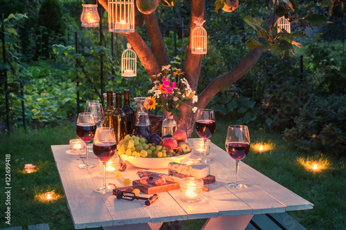 Beautiful table full of cheese and meats in garden at dusk Poster