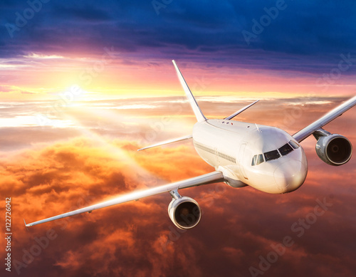 Airplane flying above clouds in dramatic sunset