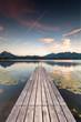 einsamer Holzsteg am See mit Seerosen, Herbst