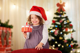 Little girl in Christmas hat of Santa Claus with a gift in hand
