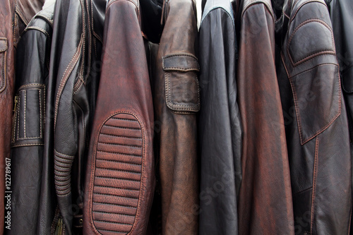 Poster Collection of leather jackets on hangers in the shop