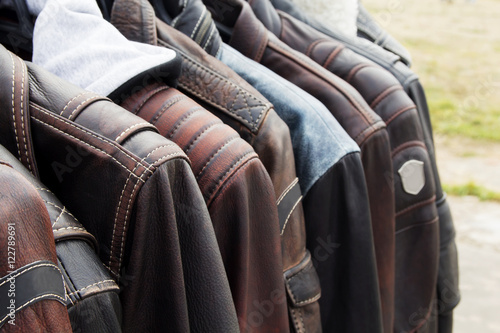 Collection of leather jackets on hangers in the shop Poster