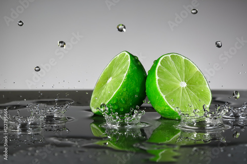 Lime with water drops on grey background