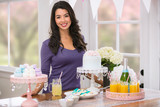 Asian woman stands next to party decoration set up table with food and drink pastel theme