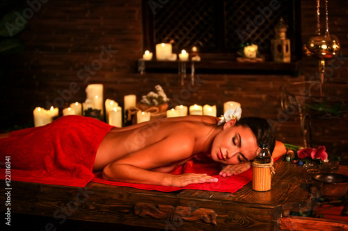 Young woman lying on wooden spa bed. Massage in spa salon. Girl on candles background in massage spa salon. Luxary interior in oriental spa salon.