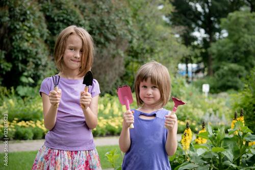 Poster Two kids showing gardening tools