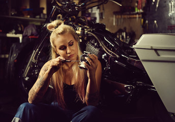 Blond woman mechanic repairing a motorcycle in a workshop