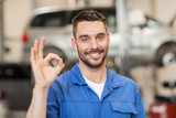 auto mechanic or smith showing ok at car workshop