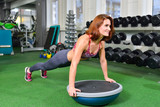 Fitness woman planking doing the body weight exercise for core strength training in gym with bosu balance trainer