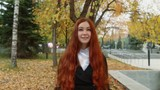 The girl with red hair in a black coat standing under falling leaves in autumn park, the average plan.