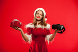 christmas, x-mas, winter, happiness concept - Beautiful young brunette with long hair in santa helper hat wearing virtual reality headset over red background gift box