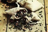 Dry green tea with flower petals in canvas bags, vintage wood ba