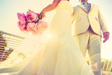 Young newlyweds with bouquet at sunset backlight - Wedding couple together after ceremony - Life and love concept with groom and bride - Lower view point composition with vignetted retro filter