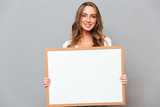 Portrait of a happy young woman holding blank board