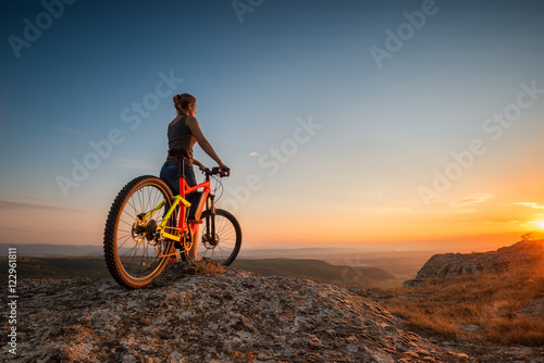 Foto op Aluminium Chocoladebruin Sunset from the top / A woman with a bike enjoys the view of sunset over an autumn forest