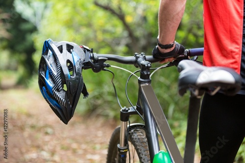 Male cyclist walking with mountain bike