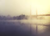 fog covers river and bridge at sunrise