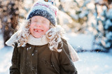 close up winter portrait of happy kid girl all covered with snow on the walk in winter snowy forest or garden. Seasonal outdoor activities.