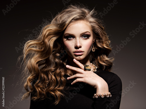 piekna-kobieta-z-dlugimi-kreconymi-wlosami-i-zlotym-jewe