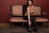Ragazza sexy seduta su un divano antico mentre si copre il seno