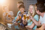 Group of friends toasting glass of beer at bar counter