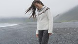 Cute beautiful woman walking on black sand beach on Iceland wearing Icelandic sweater. Pretty multiracial Asian / Caucasian female model looking shy down by the ocean sea smiling happy. 90 FPS