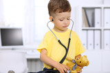 Little doctor examining a .toy bear  patient by stethoscope