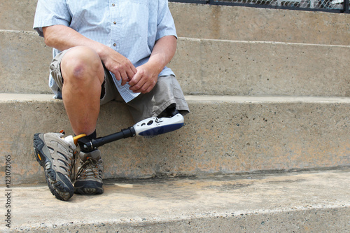 Amputee with legs crossed sitting on concrete bleachers