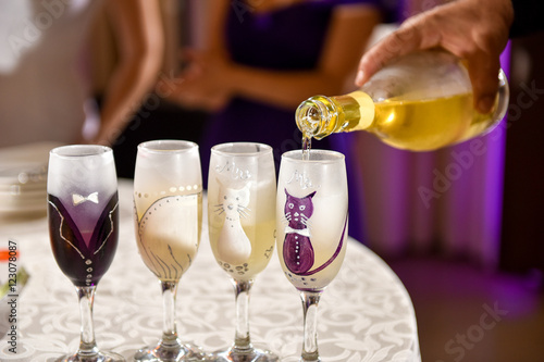 Hand man pours champagne into wedding glasses Poster