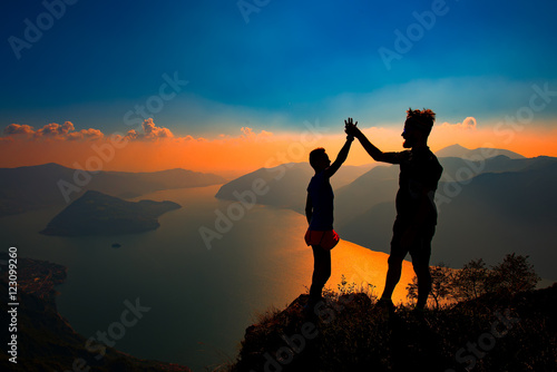 Poster A pair shake hands in victory on top of a mountain