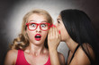 Woman sharing secret with her friend