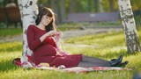 Cute pregnant woman with big belly in autumn park make hobby knitting needles