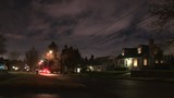 Nighttime in residential neighborhood with cars driving down street arriving home and parking.
