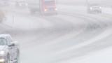Traffic driving along freeway during intense snow storm.