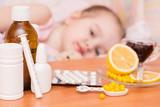 Лекарства, таблетки и витамины на фоне ребенка в кровати, болеющего ветрянкой
