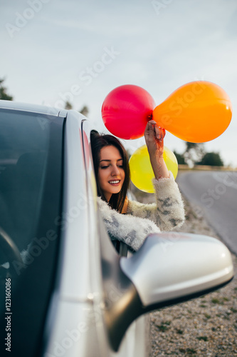 Poster Young woman having fun while holding balloons through car window.