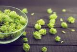Close up of green ripe hop cones in a glass bowl over dark rusti