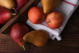 Fresh picked pears and apples in a wood crate and towel on a rustic wood table. Top view in horizontal format.