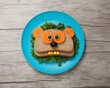 Funny panda made of bread and vegetables on plate and board