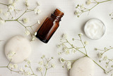 Bottle of essential oil, body care cream sample, stones, flowers. Natural skincare, top view.