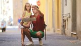 Adorable little girl and father with map of european city outdoors in Rome