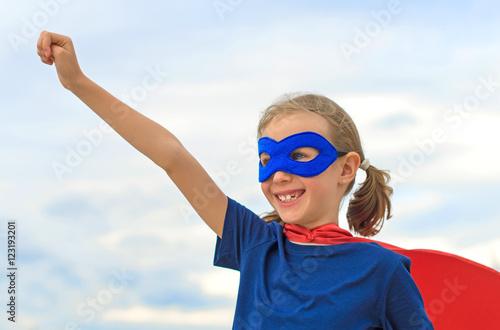 Poster Smiling superhero kid against blue sky background.