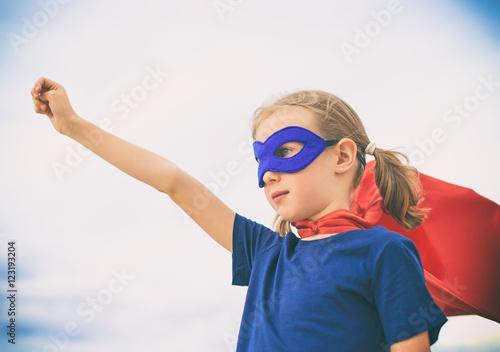 Superhero kid against blue sky background. Poster