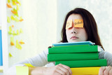 Female student napping on stack of textbooks