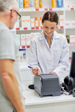 pharmacist writing check for customer at drugstore
