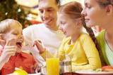 A family of four sitting in cafe, the girl feeding her brother with a spoon