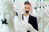 A woman standing in line of mannequins with taped mouth