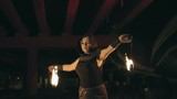 Professional female performer dancing with flaming torches at night in slow motion
