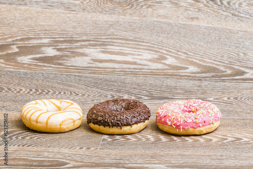Poster fresh colorful donuts, isolated on a wooden background